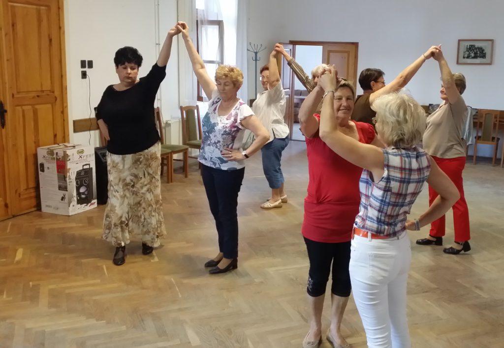 A sváb tánc oktatás résztvevői párban, egymás kezét megfogva és magasba emelve sváb zenére gyakorolnak.