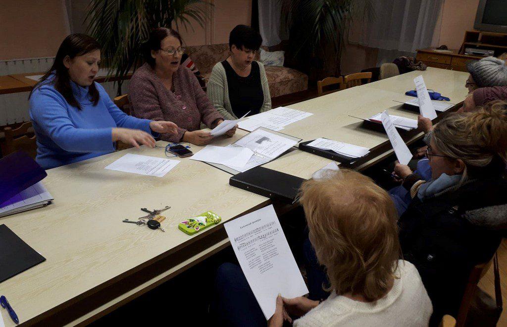 Az énekórán résztvevők kottából énekelnek, gyakorolnak a fellépésre.