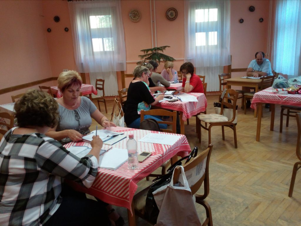 A német nyelvórán résztvevők elmélyültek dolgoznak a tanárnő által kiadott feladatok megoldásában.