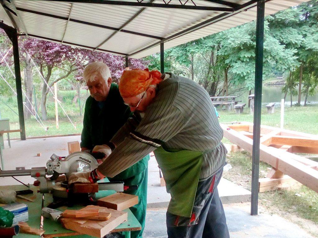 A képen a fafaragó tábor két résztvevője  munka közben látható. Körfűrésszel fadarabokat vágnak méretre.