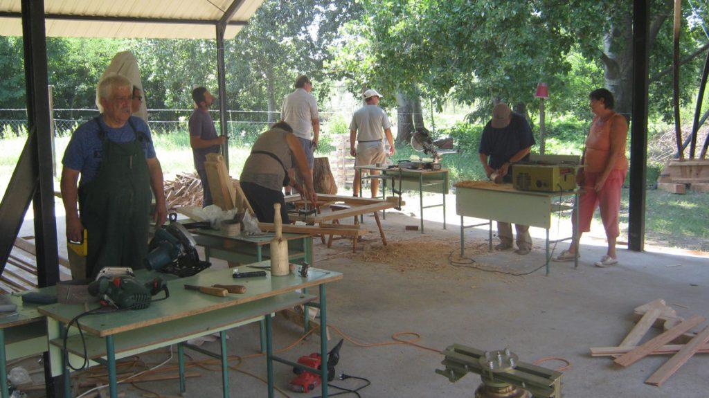 A fafaragó tábor több  résztvevője különböző munkafázisokat végez egymástól nagyobb távolságban álló asztalokon elhelyezett munkadarabokon.