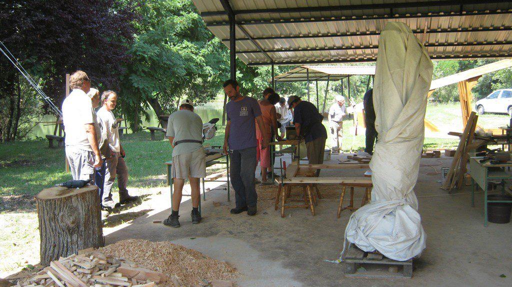 A fafaragó tábor résztvevői körben állva figyelik egyiküket fafaragás közben. Mellettük már egy elkészült kifaragott alkotás letakarva áll.