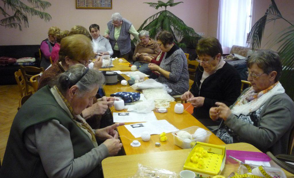 A kézműves szakkörön résztvevők egymást tanítják különböző horgolási technikákra, valamint új mintákkal ismerkednek. Többen szorgalmasan horgolnak.