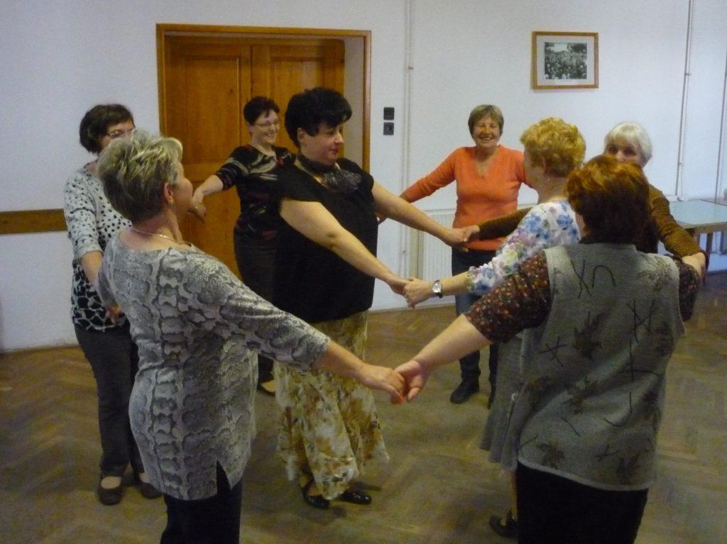 A sváb tánc oktatás résztvevői körben állva, egymás kezét fogva gyakorolják a tánclépéseket.