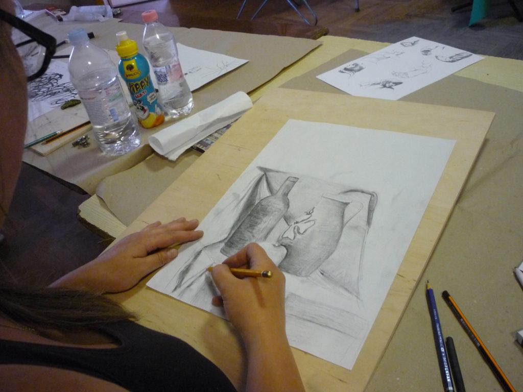 A képen a rajzoktatás egyik résztvevője látható rajzolás közben. Beállított csendéletet rajzol ceruzával, melyen borosüveg, kancsó és alma látható.