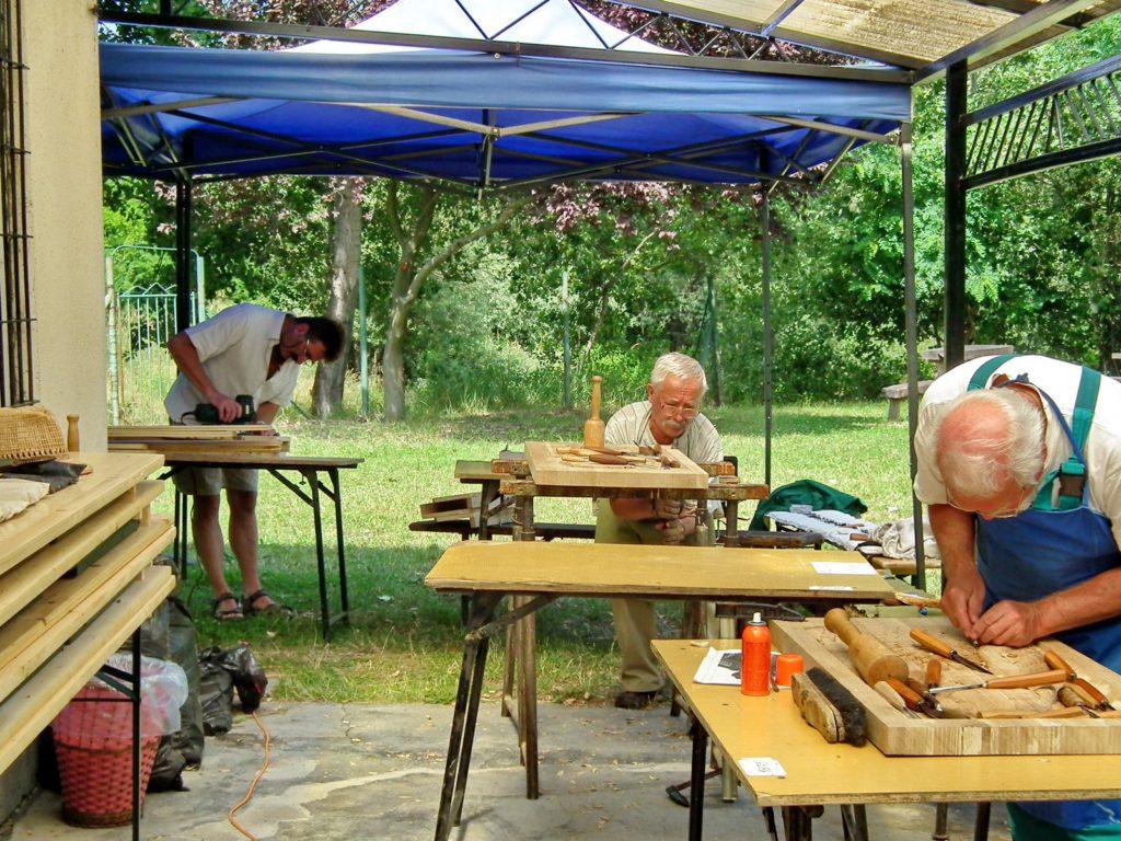 A fafaragó táborban résztvevők az oktató vezetésével különböző fázis folyamatokat végeznek az előttük lévő fatáblákon. Van aki vésővel, gyaluval,egyéb fafaragó eszközzel dolgozik.