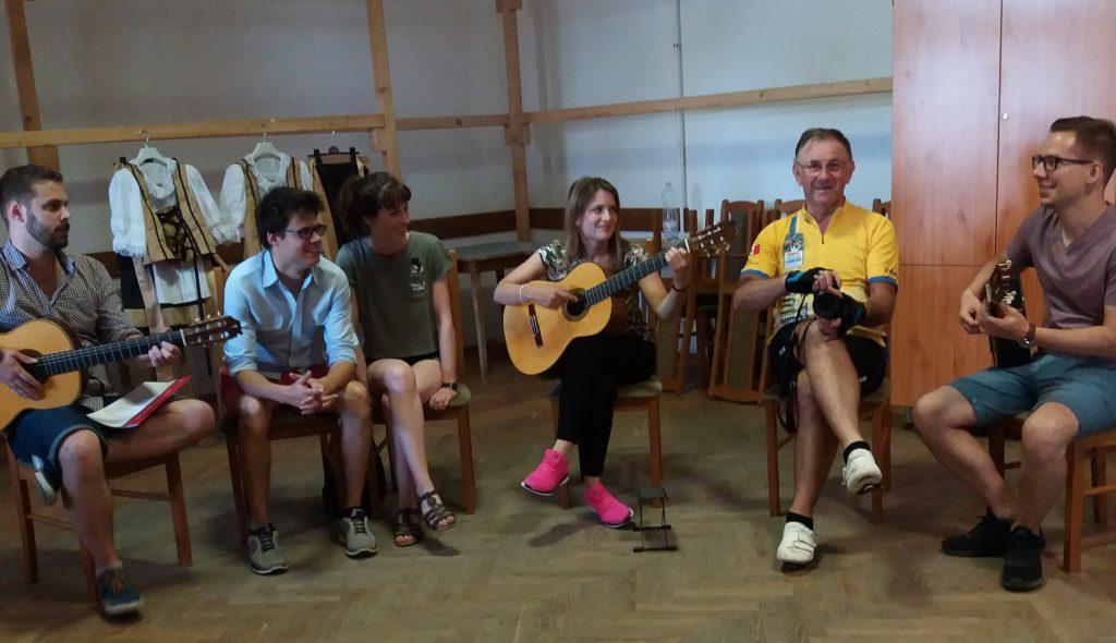 A gitároktatás résztvevői, fiatalok és idősebbek egyaránt, kezükben gitárral figyelmesen hallgatják az oktató szavait.