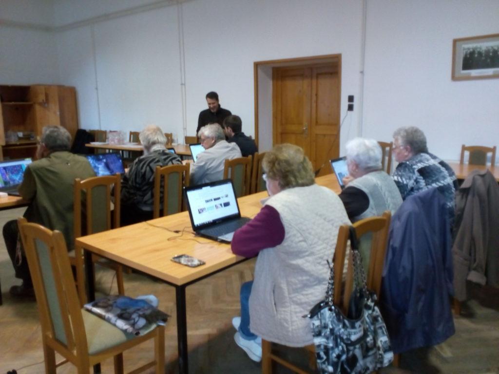 Az informatika tanfolyamon résztvevők asztaloknál ülnek, ellőttük laptop. Figyelmesen hallgatják az oktató előadását a számítástechnikai eszközök használatáról.
